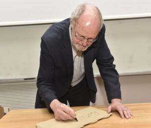 """פרופ' גראבס חותם את שמו על הלוחית שתצורף ל""""קיר גדולי הכימיה"""""""