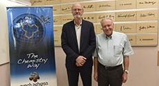 """פרופ' אפלויג ופרופ' גראבס ליד """"קיר גדולי הכימיה"""""""