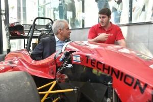 ראש עיריית שיקגו רם עמנואל בוחן מקרוב את מכונית הפורמולה של הטכניון ומקבל הסבר מהסטודנט אלן אלטרי