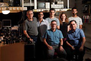 """יושבים: פרופ'-מחקר מוטי שגב (מימין) ופרופ' ארז חסמן. עומדים מימין לשמאל: תומר סתיו, דקלה אורן, ארקדי פאירמן, אלחנן מגיד וד""""ר ולדימיר קליינר"""