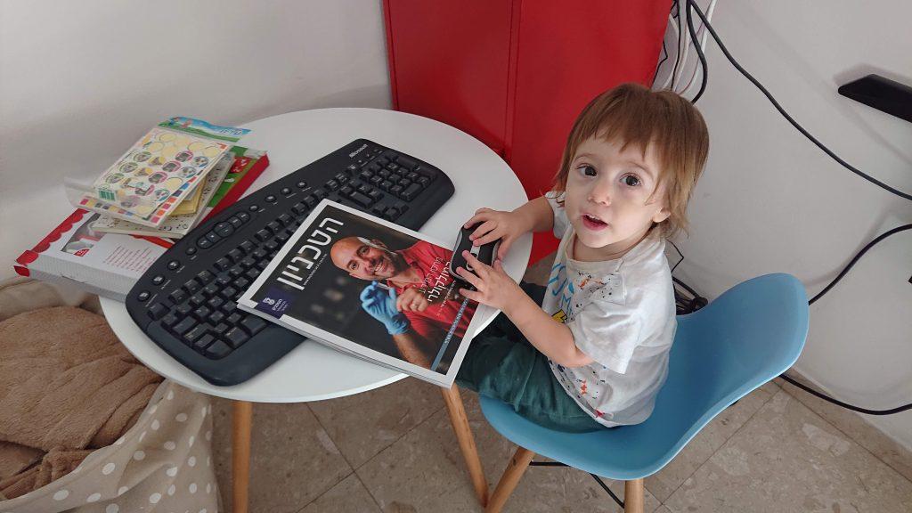 בתמונה: איתמר ענבי הצעיר מעיין בגיליון הנוכחי, שעל כריכתו מופיע אביו ליאון ענבי מהפקולטה למדעי המחשב