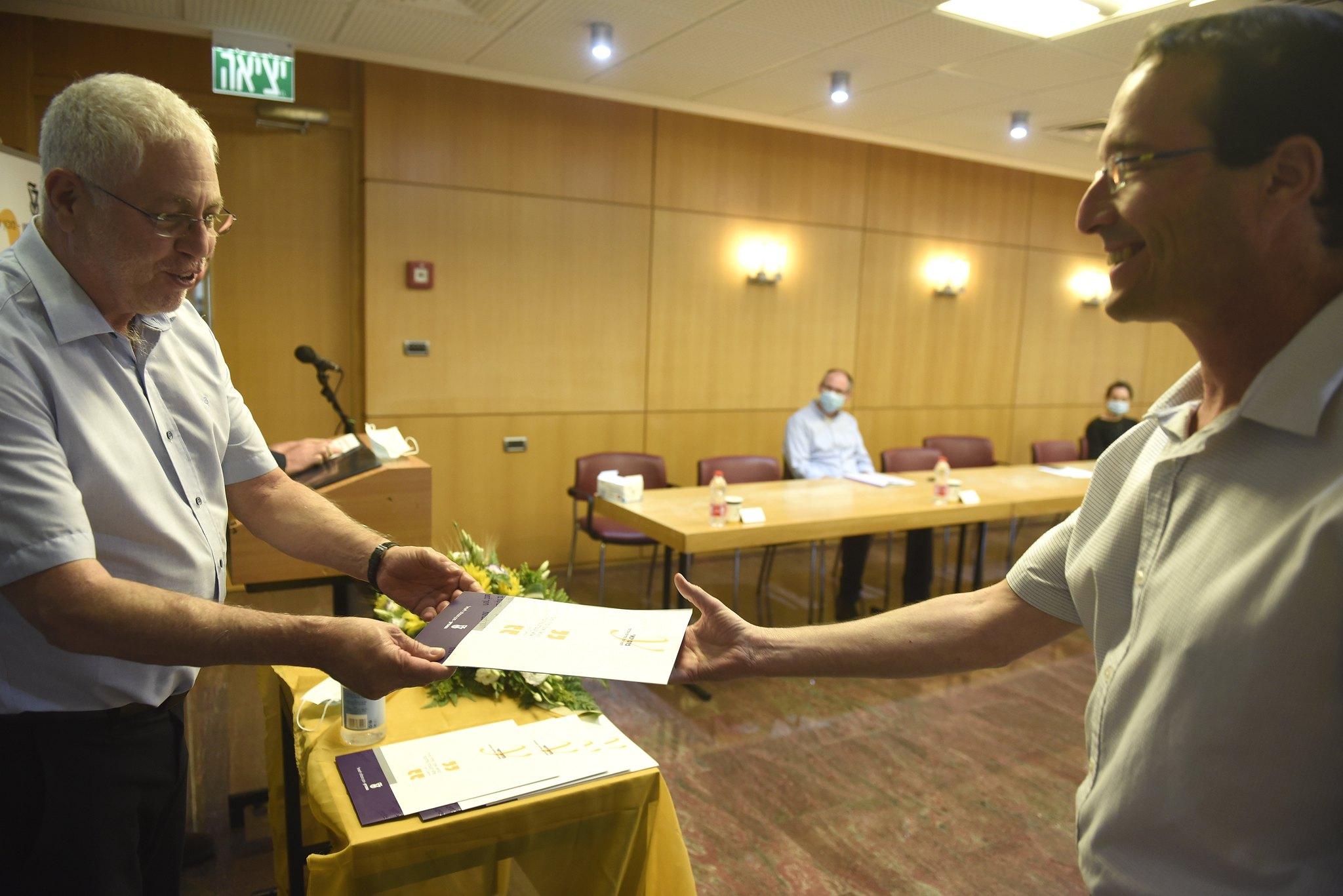 """נשיא הטכניון פרופ' אורי סיון מעניק את הפרס לפרופ""""ח יואב ליבני מהפקולטה להנדסת ביוטכנולוגיה ומזון"""