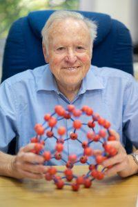 פרופ'-מחקר אפלויג עם דגם של מולקולת הפולרן שעמדה במרכז פרס נובל בכימיה לשנת 1996